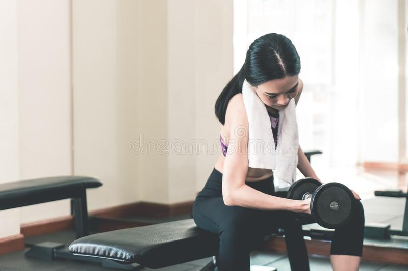 Small thin asian woman is lifting dumbbell in fitness club. Small thin asian woman is lifting dumbbell in fitness royalty free stock photography