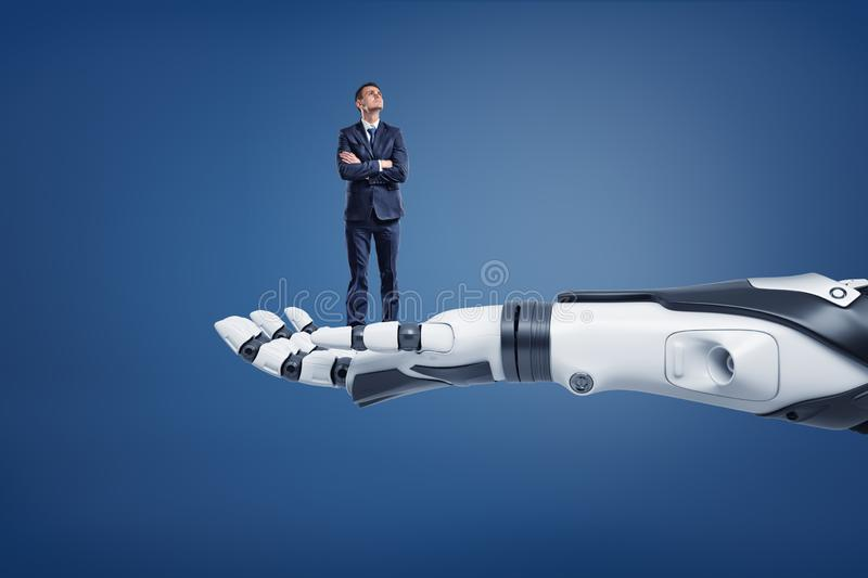 A small thinking businessman looks up while standing on a huge robotic arm. Regarding new technologies. Business and high-tech. Scientific progress in office stock photo