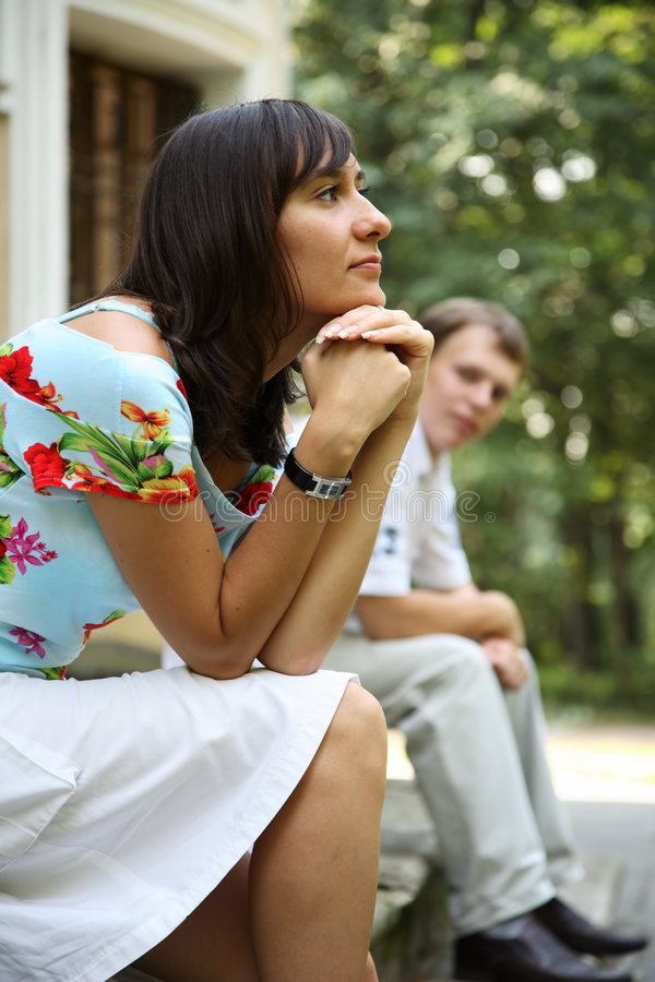 Small tiff. Young woman and man sitting on marble steps in park, selective focus royalty free stock photography