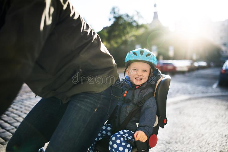 A small toddler boy sitting in bicycle seat with father outdoors in city. royalty free stock photography