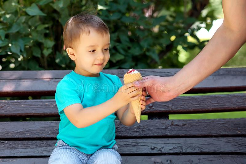 Small toddler boy sitting on bench in park and receiving ice-cream from hand of father in summer or autumn day outdoors. royalty free stock photo
