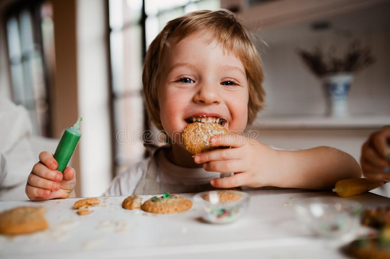 A small toddler boy sitting at the table, decorating and eating cakes at home. A small happy toddler boy sitting at the table, decorating and eating cakes at royalty free stock photos