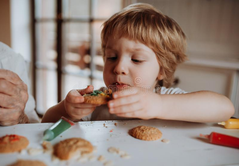 A small toddler boy sitting at the table, decorating and eating cakes at home. A small happy toddler boy sitting at the table, decorating and eating cakes at royalty free stock images