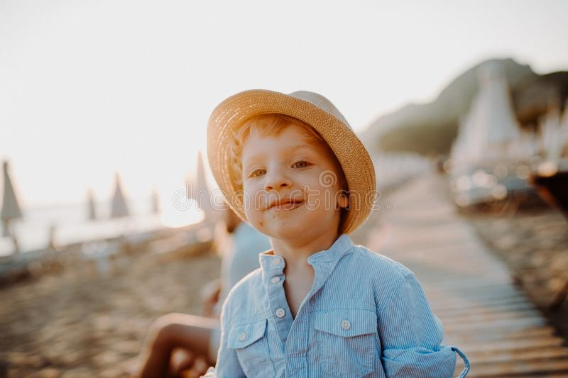 A small toddler boy standing on beach on summer holiday at sunset. royalty free stock image