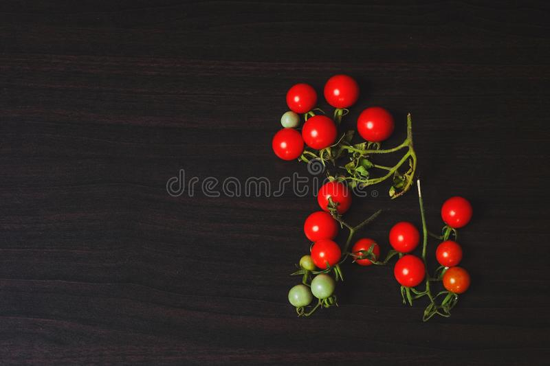 Small Tomato on black wood background.Food stock photos