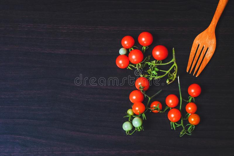 Small Tomato on black wood background.Food royalty free stock photos