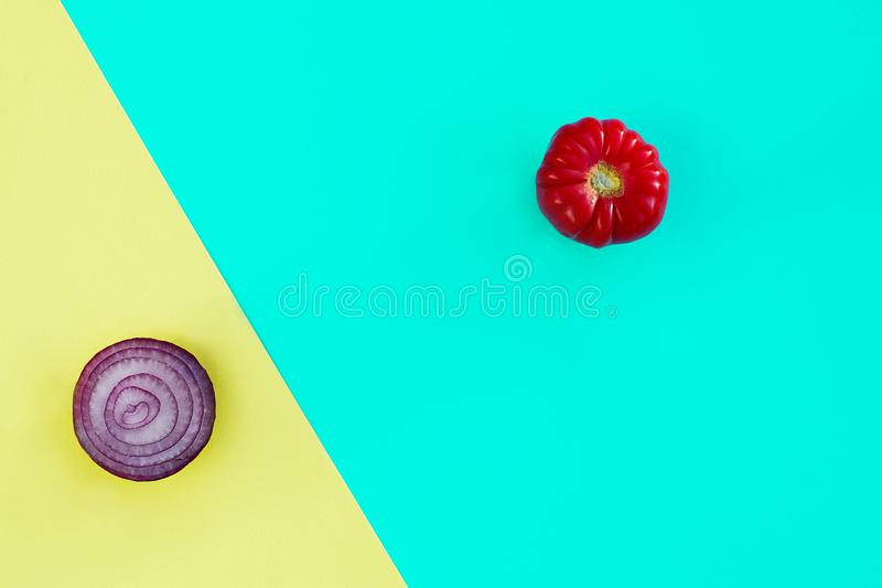 Small tomato on blue and red onion on yellow background royalty free stock image