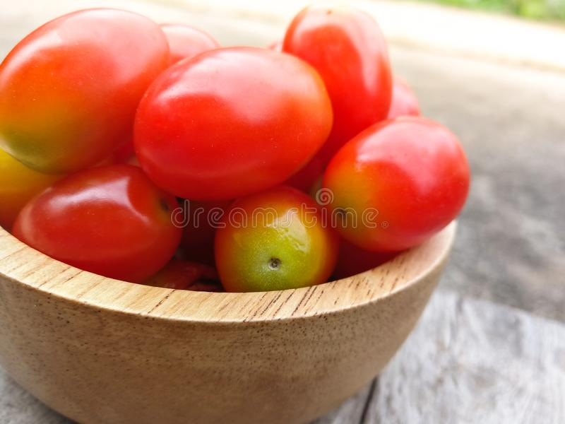 Small tomato. Red small tomato in wood cup stock images