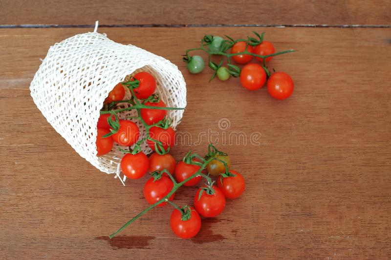 Small Tomato spill out of basket.Food. Concept royalty free stock photo