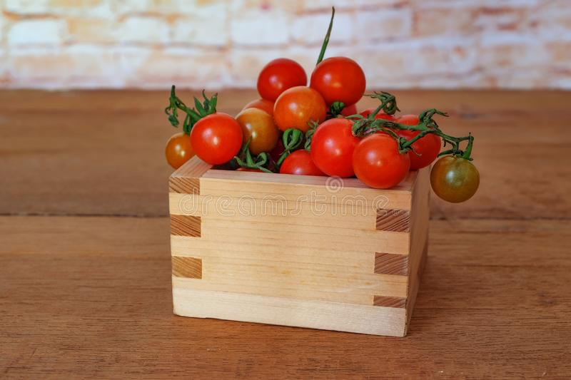 Small Tomato spill out of wood box.Food. Concept stock photography