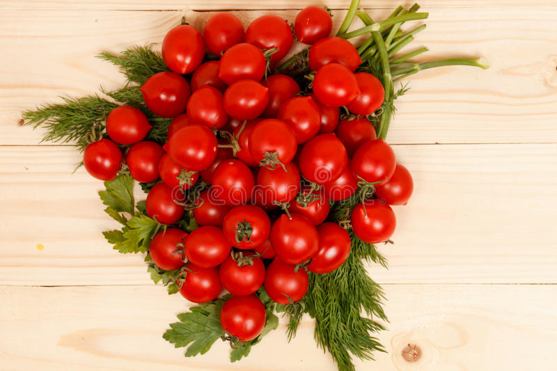Small tomatoes and fresh herbs on wooden background royalty free stock photos