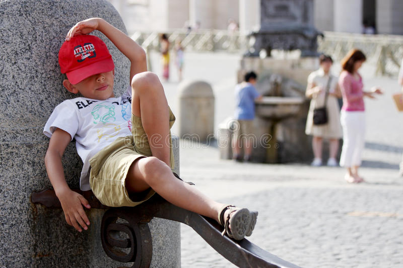 Small boy tourist rests. A small tourist resting near a fountain in Vatican City (Rome) / A little boy is lying on top of an iron beam royalty free stock photos