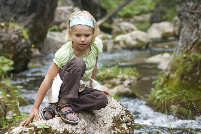 Small tourist sitting by a mountain river royalty free stock photos