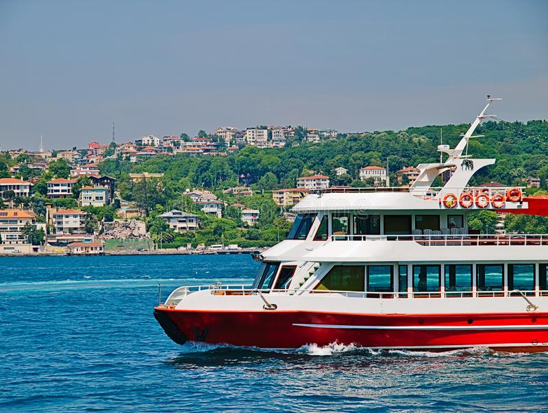 Small touristic red cruise ship. With no passengers at Bosporus strait and residential building at coast royalty free stock photography