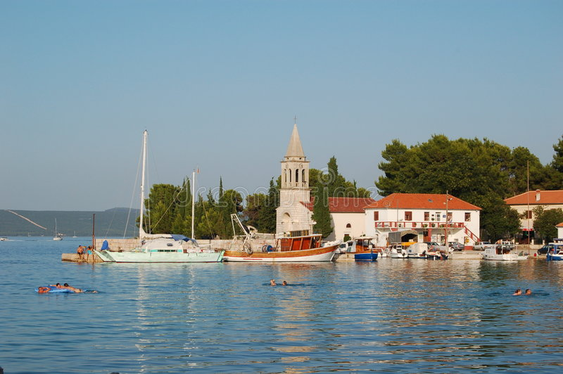 Small town coast. Adriatic summer resort Zdrelac, island Pasman, Dalmatia, Croatia. People are swimming in the blue, clear sea. In the background: a fishing boat stock photo