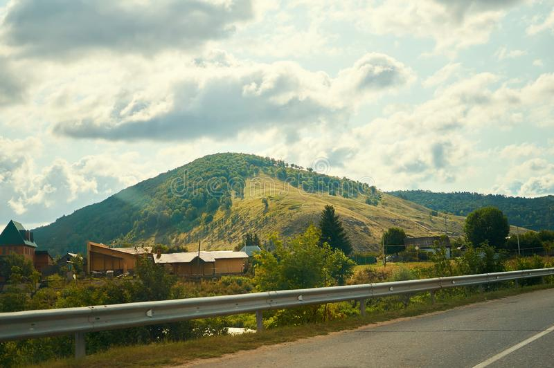 A small town near the hill with an asphalt road. royalty free stock images