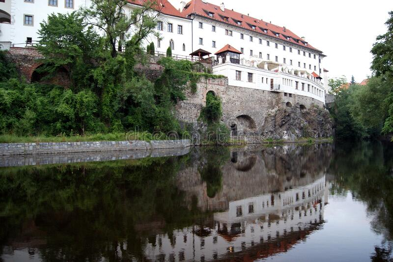 Southern wall of the former Jesuit Monastery reflecting in the Vltava River at dusk, Cesky Krumlov, Czechia. Southern wall of the former Jesuit Monastery stock photos