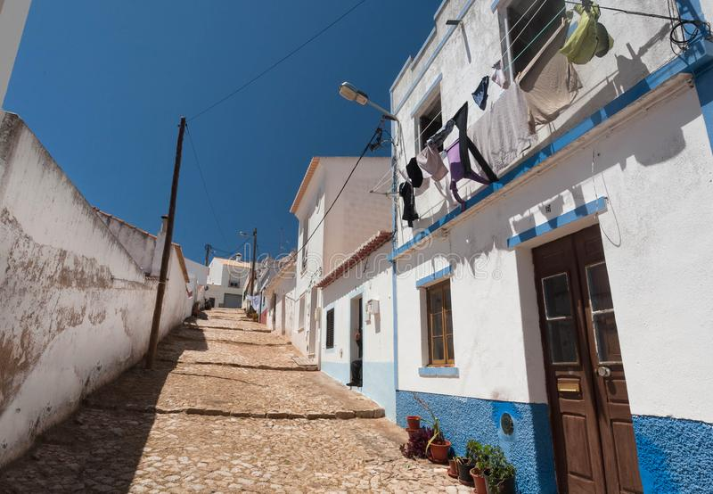 Small town in south Portugal with narrow streets and white houses under blue sky. Sunny village of Algarve region royalty free stock images
