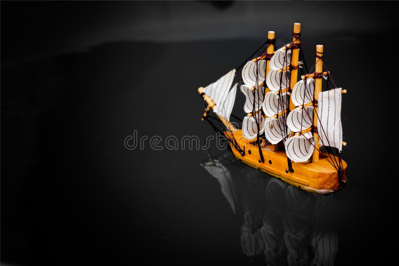 Small toy boat in the water with big waves  white wooden ship model sailboat background gold. Antique object vintage travel miniature retro classic royalty free stock photos