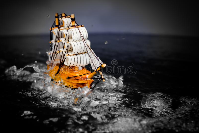 Small toy boat in the water with big waves  white wooden ship model sailboat background gold. Antique object vintage travel miniature retro classic royalty free stock photography