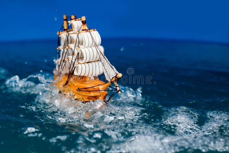 Small toy boat in the water with big waves  white wooden ship model sailboat background gold. Antique object vintage travel miniature retro classic stock photos