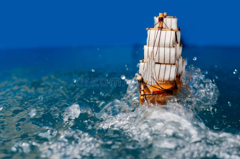 Small toy boat in the water with big waves  white wooden ship model sailboat background gold. Antique object vintage travel miniature retro classic stock image