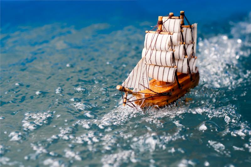 Small toy boat in the water with big waves  white wooden ship model sailboat background gold. Antique object vintage travel miniature retro classic stock photo