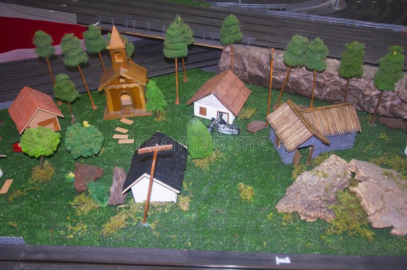 Small toy church, different houses and trees around. Front up view stock photography