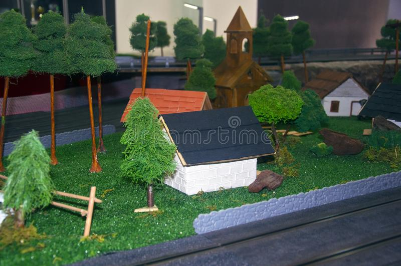 Small toy church, different houses and trees around. Left down view royalty free stock photography