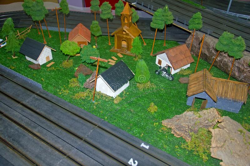 Small toy church, different houses and trees around. Right up view stock photos