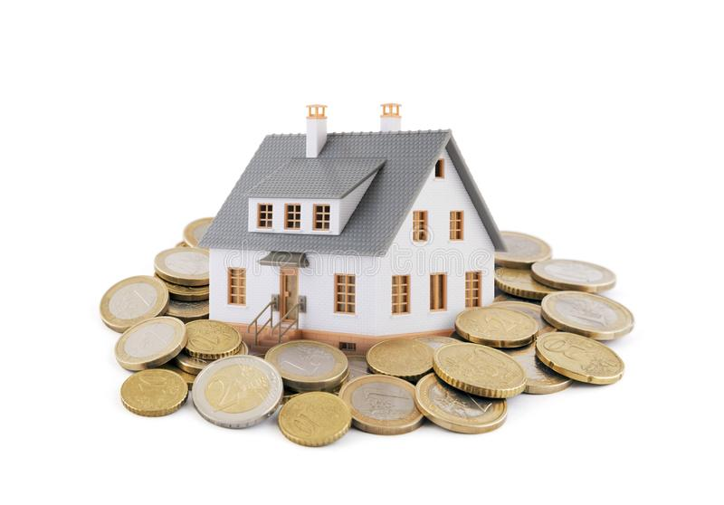 Small toy house with euro coins stock photo