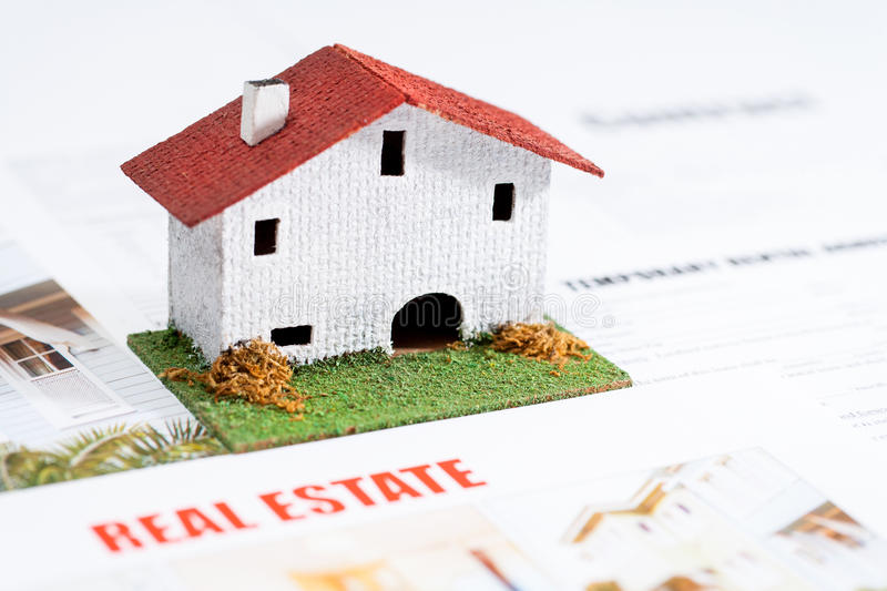 Small toy house on real estate documents. Close up of small toy house on real estate documents stock images
