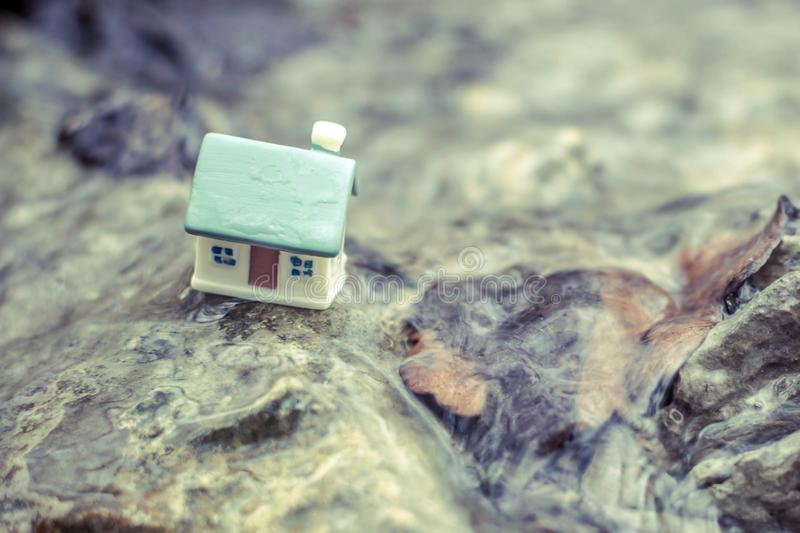 Toy house. Small toy house on a stone, home, real, estate, background, model, building, miniature, mortgage, hand, white, sale, insurance, concept, construction stock photos