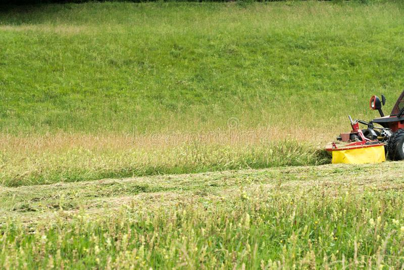 Small tractor with mower in front cutting a steep hillside wildflower meadow in the Alps for hay stock images