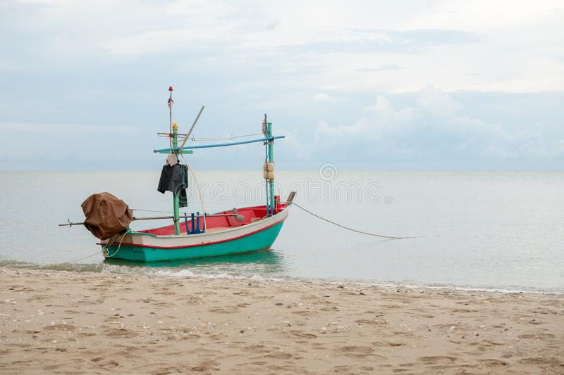Small traditional fishing boat floating in the sea at coast with calm surface on ocean and clouded sky royalty free stock photography
