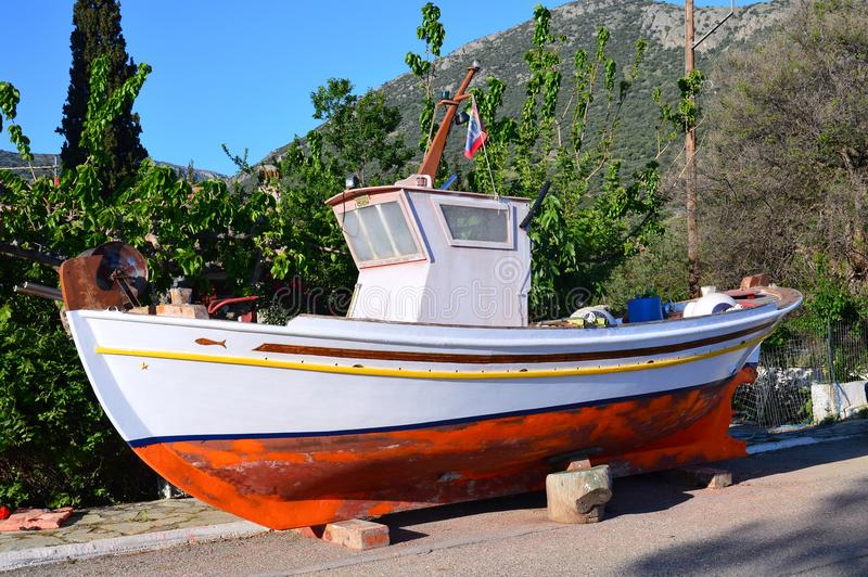 Maintenance on Greek Wooden Fishing Boat, Greece. A small traditional Greek wooden fishing boat, or caique, with a small cabin, on land for Spring cleaning royalty free stock photo