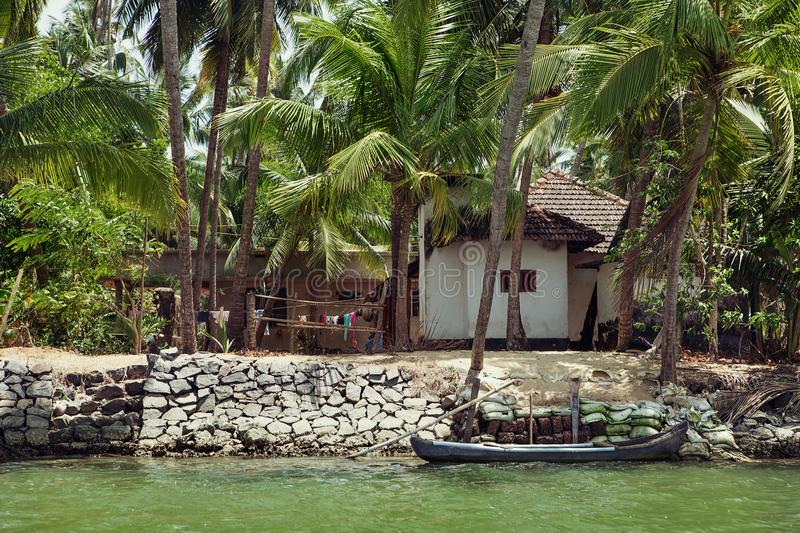 Small traditional house and old boat on the river in Kerala, Ind stock photo