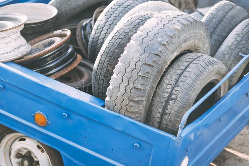 small trailer, blue color. it contains a lot of old tires and wheels. concept change tires on the car royalty free stock photography