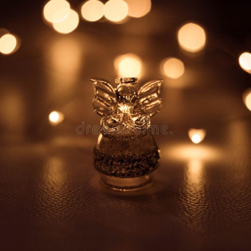 A small transparent angel with wings holds a star on a dark brown background with bright lights bokeh. Glass angel close up, macro stock photography