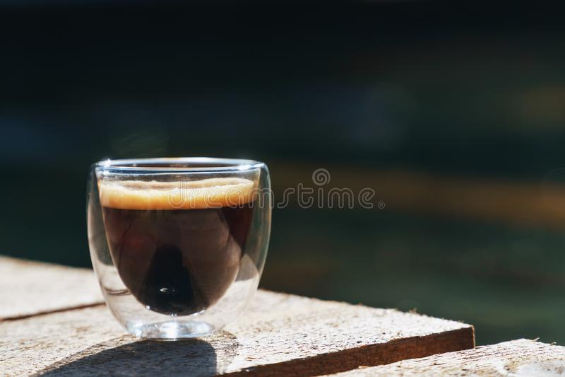 Small transparent double wall glass cup of fresh brewed coffee placed on a natural rough wooden surface in front of a decorative stock image