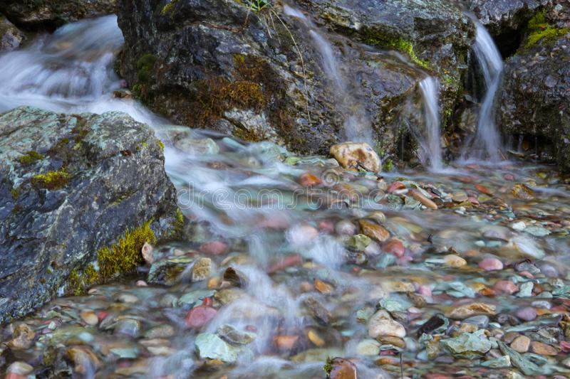 Small Trickling Waterfall. A trickling waterfall flowing over colorful rocks royalty free stock photo