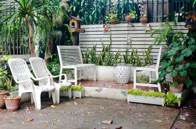 Small tropical house balcony with green plants in pots and white bench stock images