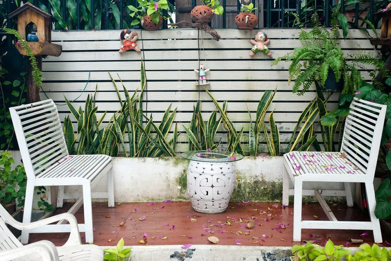 Small tropical house balcony with green plants in pots and white bench. In the garden royalty free stock photos