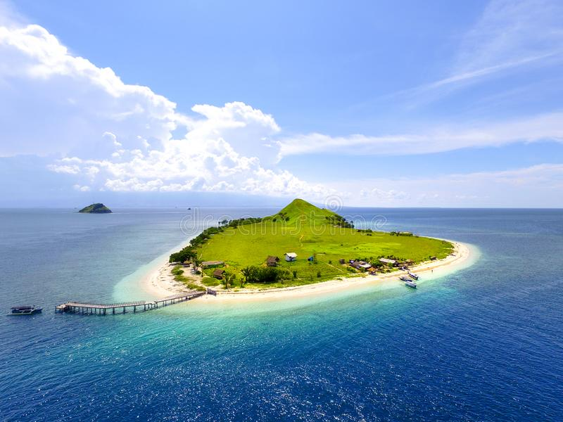Small tropical island with white green savannah and sandy beach. Beautiful Kenawa island view from above. Nature of the Indonesia royalty free stock photography