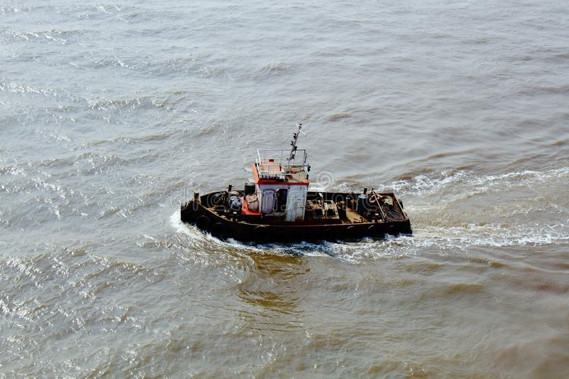 Small tug boat swings in the waves. Of the Arabian sea like a sliver. Top view royalty free stock image