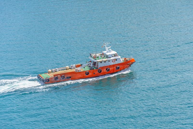 Small tug ship sails in a harbor bay in the mediterranean sea.  royalty free stock image