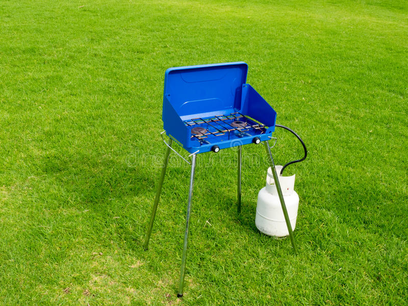 Small two flame gas cook stove on green lawn stock photos
