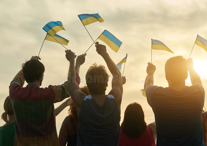 Small ukrainian flags. Back view. Blue and yellow flags. Evening sky bakground stock images