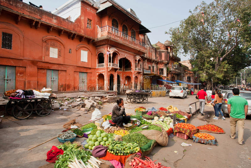 Small vegetable market with cucumbers, peppers and tomatoes past the walls of the Pink City. JAIPUR, INDIA: Small vegetable market with cucumbers, peppers and stock image