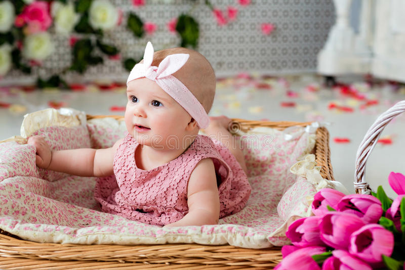 Small very cute, big-eyed little girl in a pink dress lying in a royalty free stock image